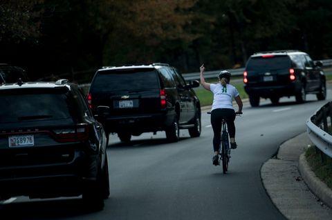 Juli Briskman auf einem Fahrrad. Sie zeigt dem vorbeifahrenden Donald Trump den Mittelfinger.