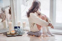 Weihnachten alleine: Frau sitzt am Fenster