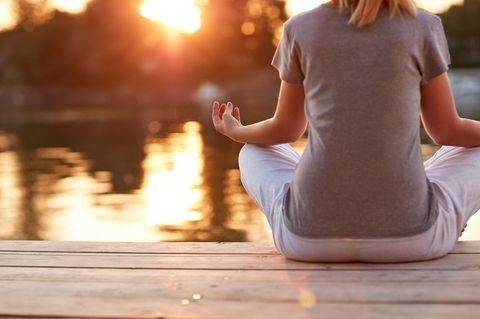 Chakren: Frau meditiert am Wasser