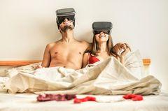 VR Porn: Paar sitzt mit VR-Brillen im Bett