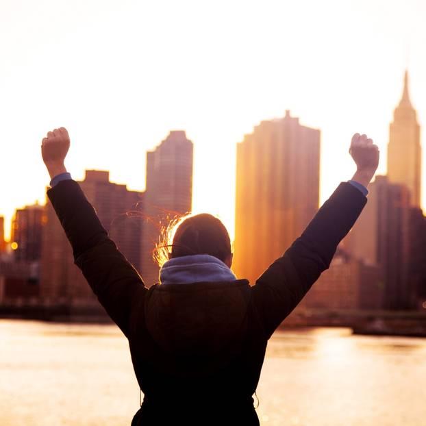 Ziele setzen und erreichen: Frau reißt die Arme hoch