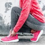 Regelmäßiger Sport: Frau bindet Turnschuhe