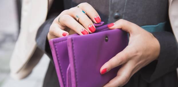 Geldsorgen loswerden: Frau öffnet ihr lila Portemonnaie