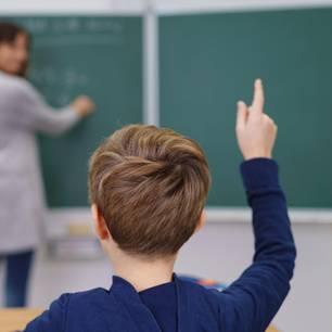 Ein Junge hebt in einem Klassenzimmer die Hand.