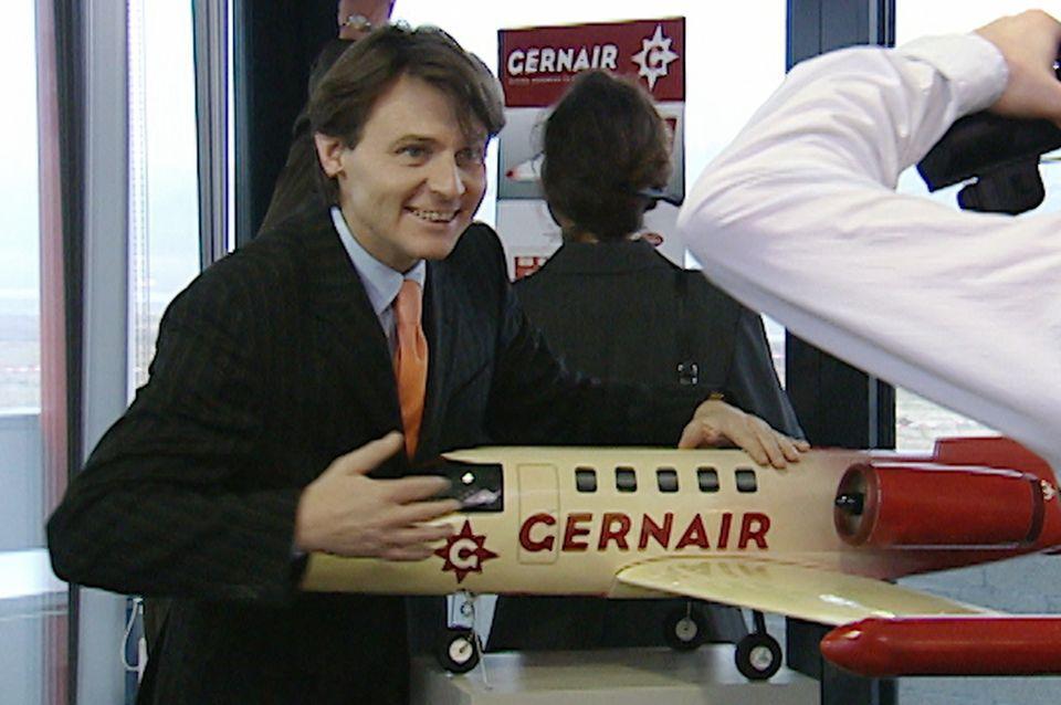"""Jo Gerner (Wolfgang Bahro) mit einem Flugzeug-Modell seiner """"Gernair""""-Flotte."""