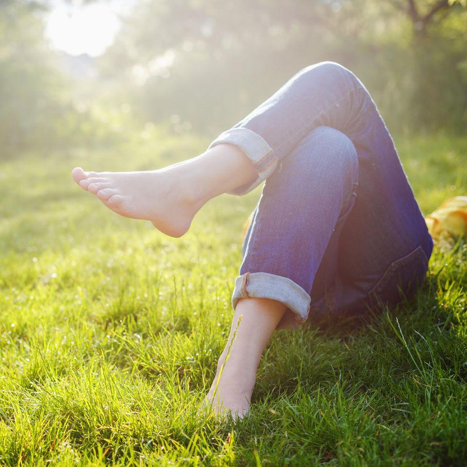 Zitate übers Faulenzen: Frau liegt im Gras