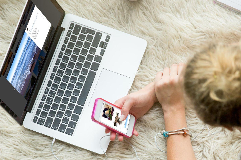 Instagram: Eine junge Frau vor Laptop und Smartphone