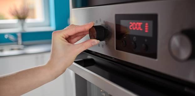 Backofen vorheizen: Frau wärmt den Ofen zum Backen vor