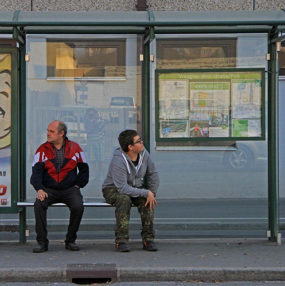 Bußgeldbescheid: Zwei Menschen warten an einer Bushaltestelle.