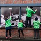 """Greenpeace-Aktivisten bringen Aufkleber mit der Aufschrift """"Mit Tierleid"""" auf Fleischpackungen bei Lidl an."""