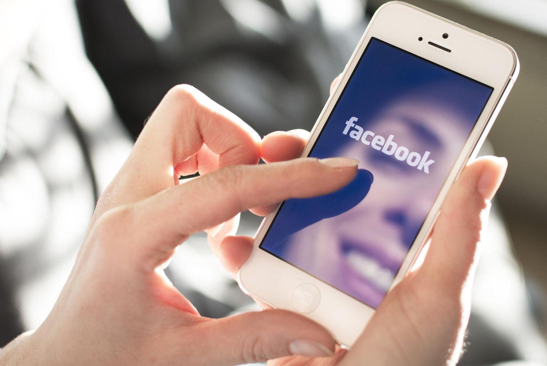 Facebook verlangt Selfie: Eine Person mit Smartphone, auf dem sich das Gesicht spiegelt