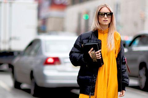 Frau trägt gelbes Maxikleid und schwarze Daunenjacke