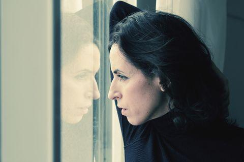 Torschlusspanik: Frau steht am Fenster