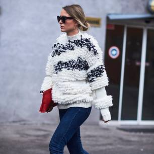 Frau trägt Oversized-Pullover und Jeans