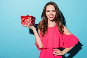 Mädchen trägt Geschenk in der Hand