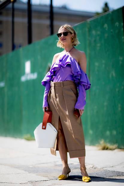 Frau trägt lila Bluse und Rock