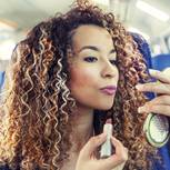 Frau schminkt sich im Zug