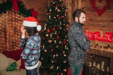 Streit zu Weihnachten: Paar vor dem Weihnachtsbaum