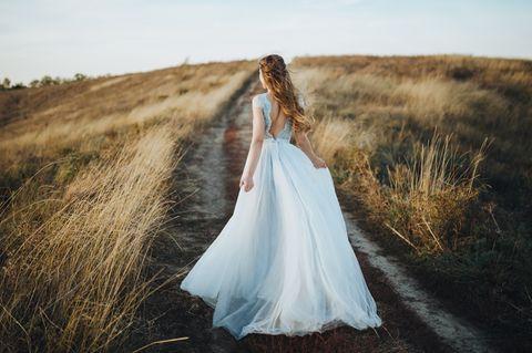 Frau trägt langes weißes Brautkleid