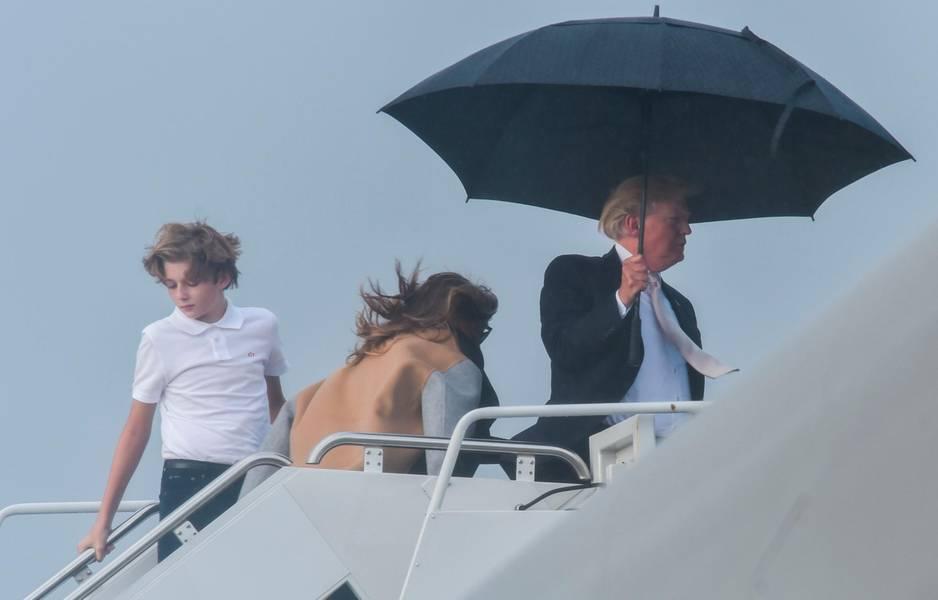 Donald Trump, Sohn Barron und Gattin Melania. Und ein Regenschirm.