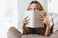 Frau liegt auf dem Sofa und liest