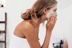 Frau legt eine Gesichtsmaske auf