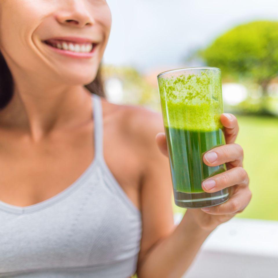 Kollagendrink: Frau hält grünen Smoothie in der Hand