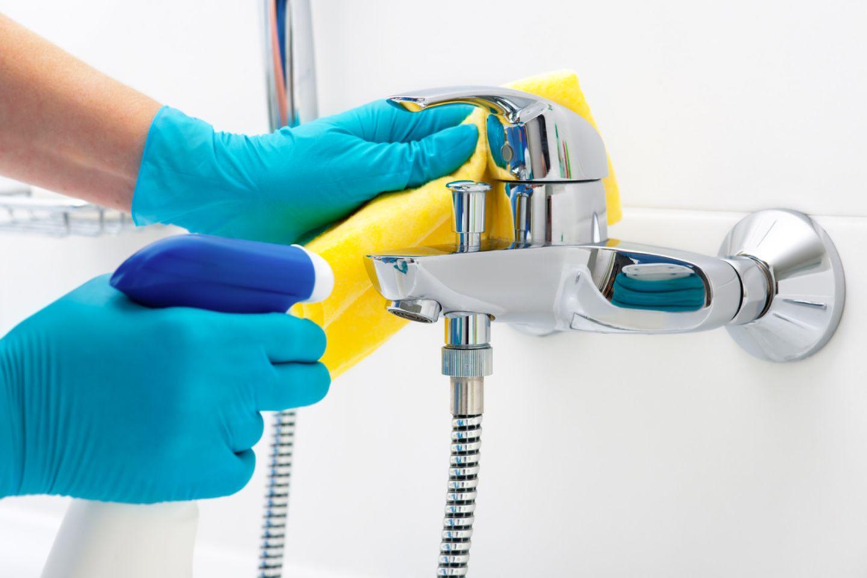 Bad putzen: Dusche und Wasserhahn mit Putzmittel reinigen