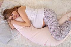26. SSW: Schwangere schläft mit Stillkissen