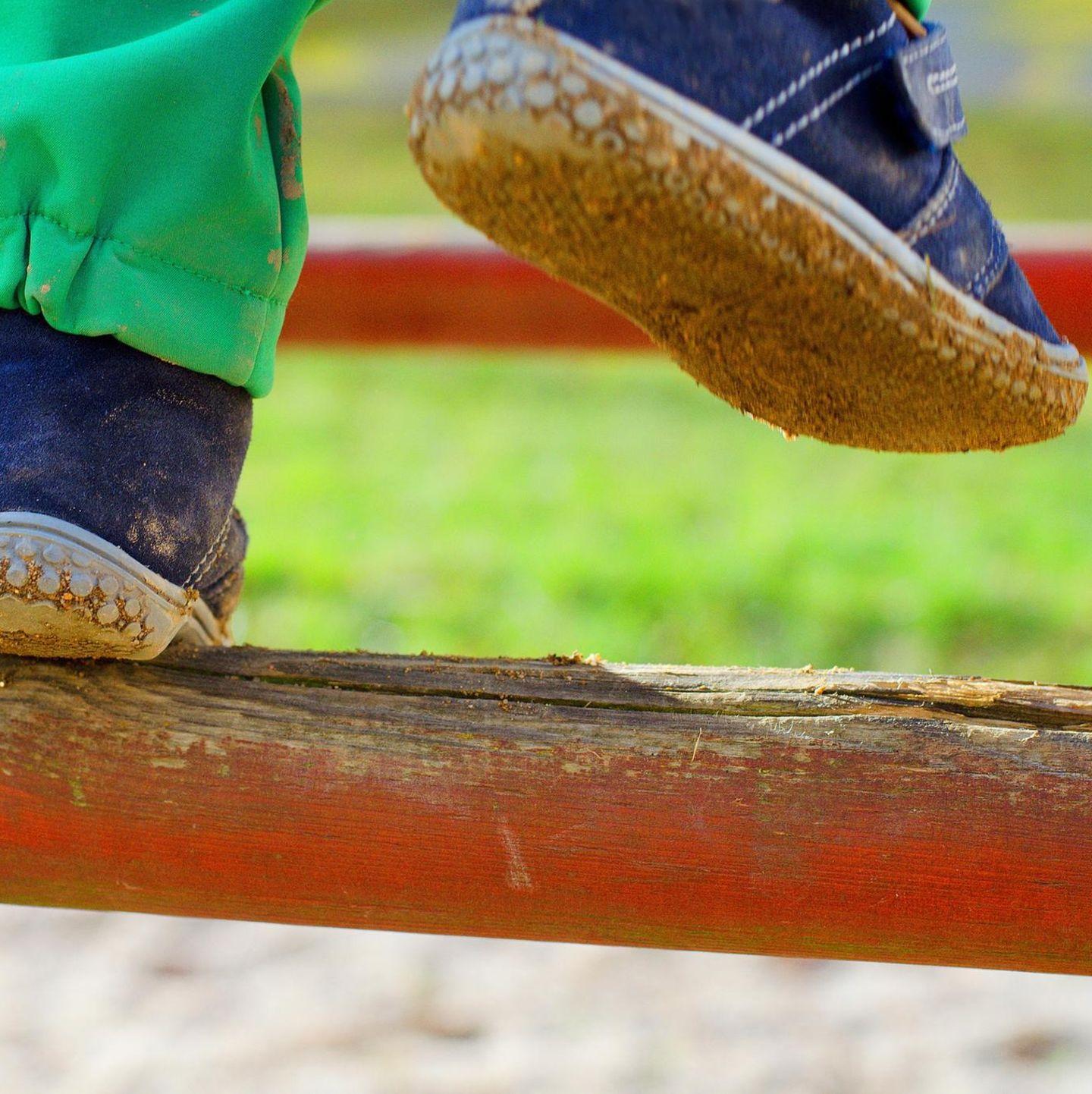 Kleinkindfüße in Schuhen auf Klettergerüst