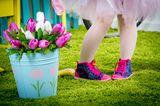 Kleinkind in Tutu mit Sneakern auf Rasen