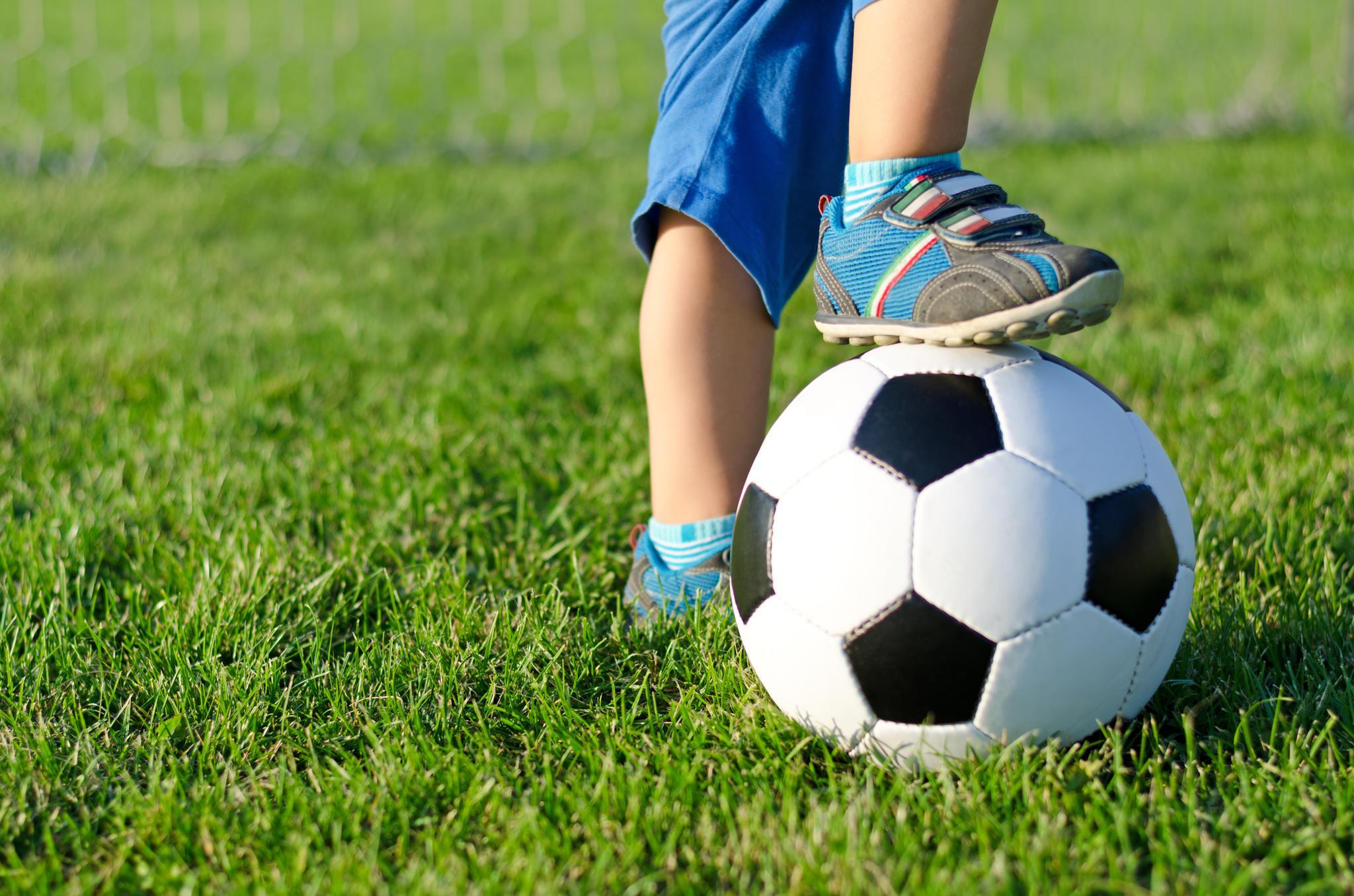 Kind steht auf Fußball mit Sneaker