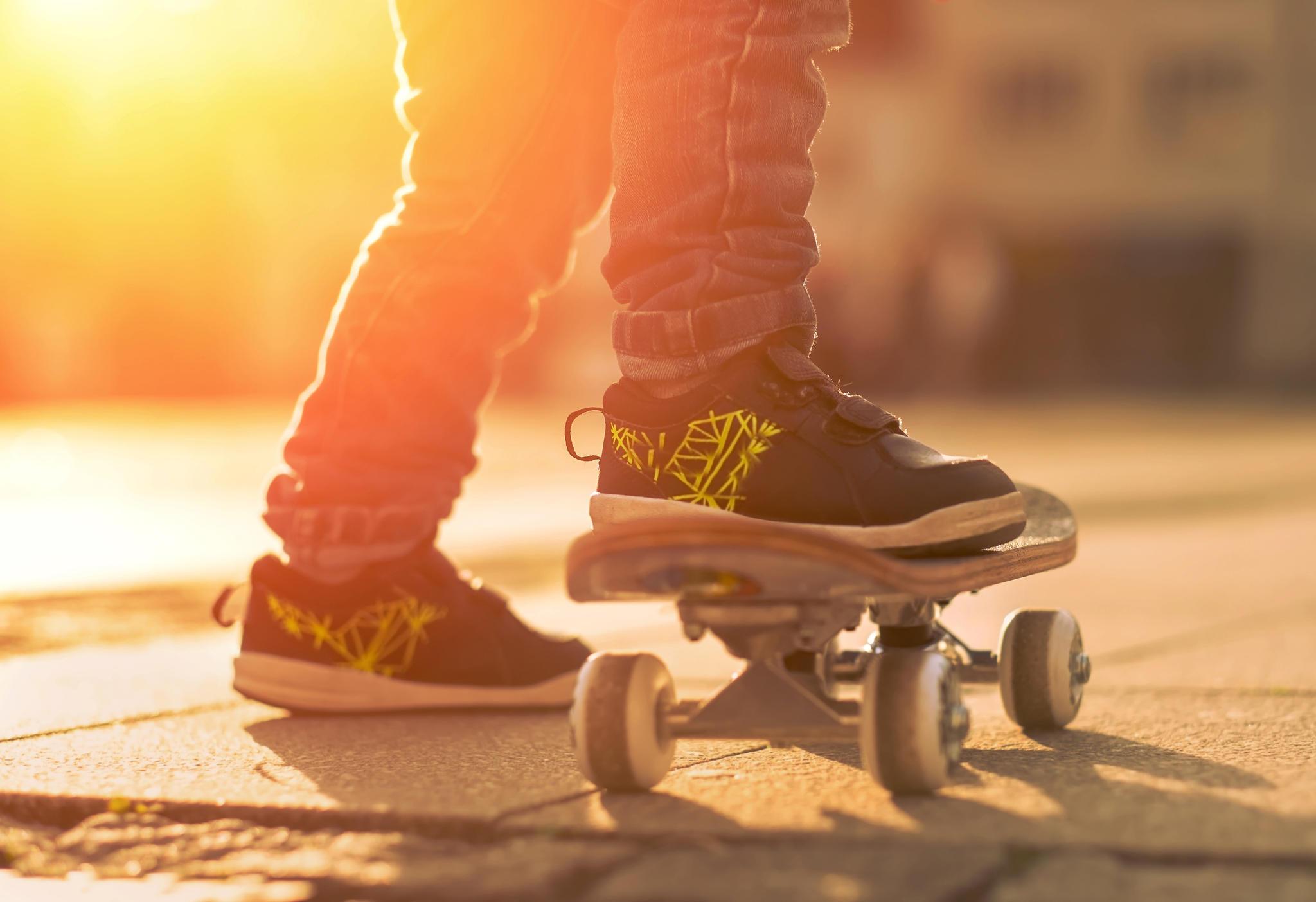 Kind in Sneakern auf Skateboard