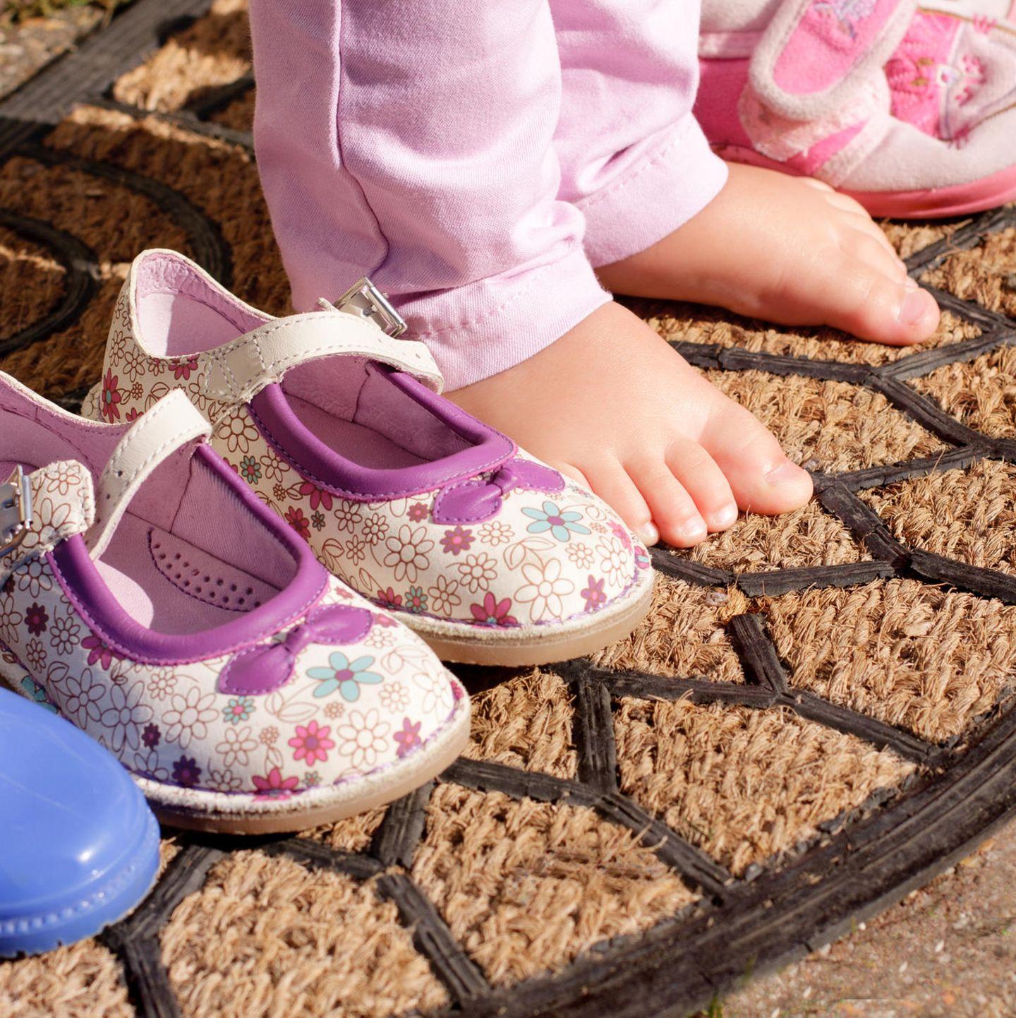 Kinderfüße nackt neben Schuhen