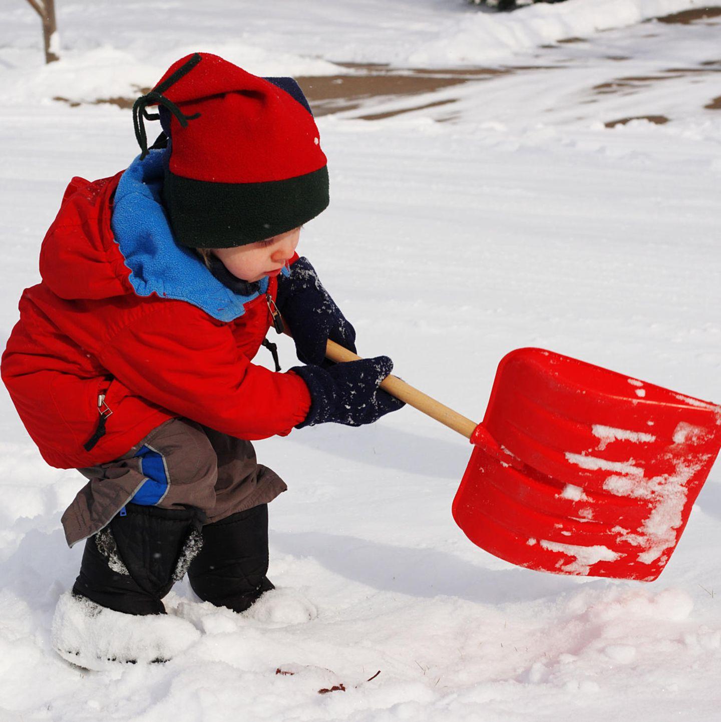 Kind mit Stiefeln  im Schnee mit Schippe