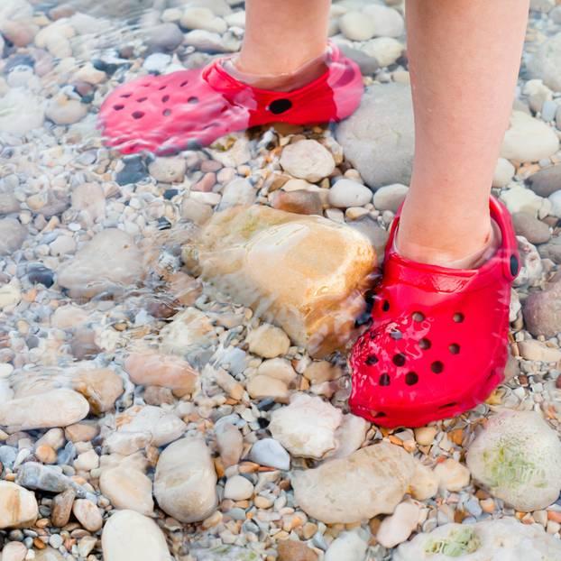 Kinderfüße in Gummischuhen am steinigen Strand