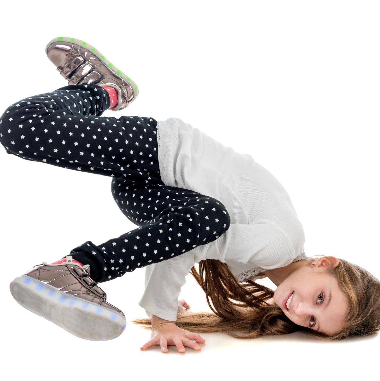 Mädchen in Turnschuhen macht Breakdance
