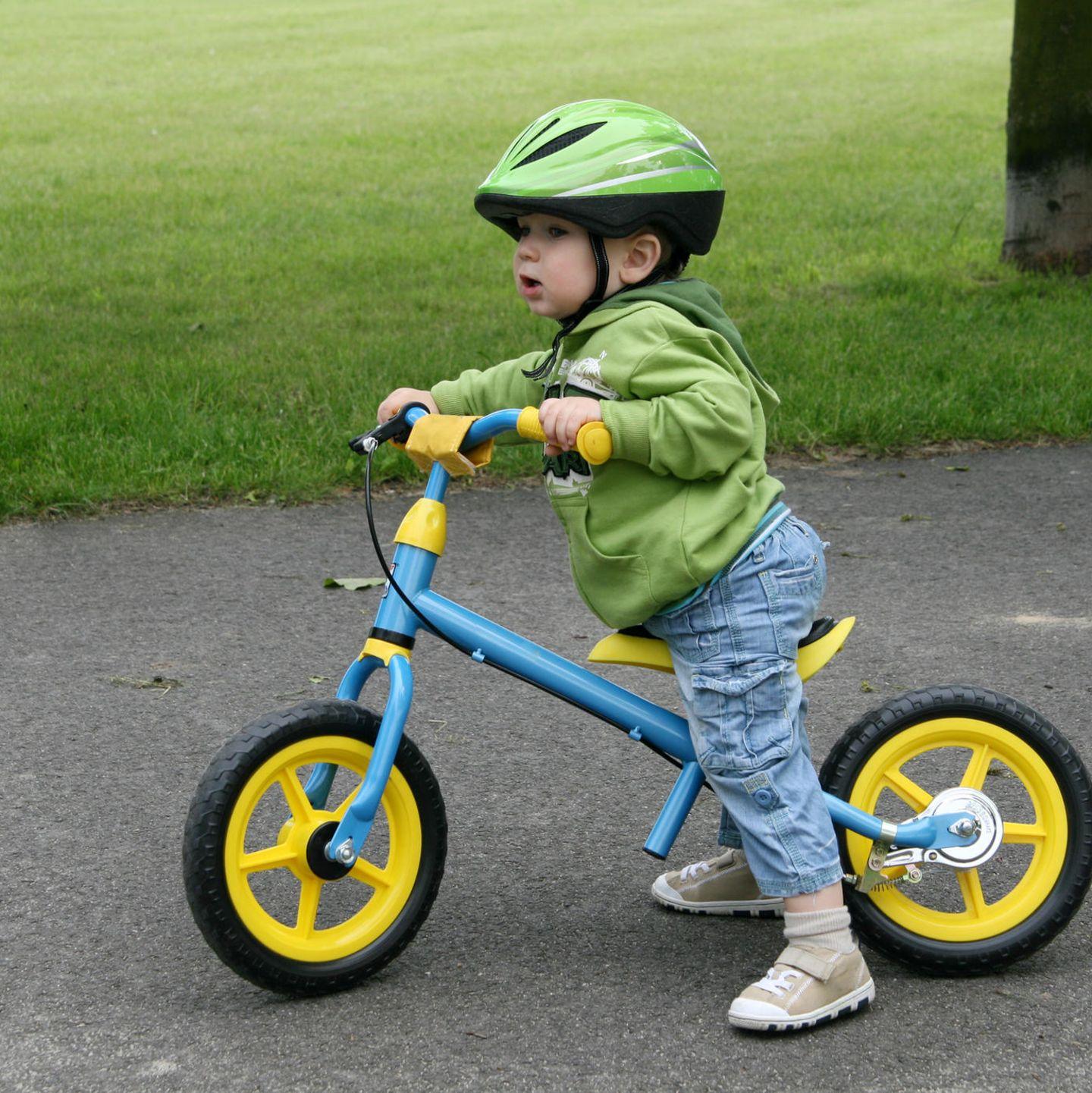 Kind auf Laufrad mit Helm und festen Schuhen