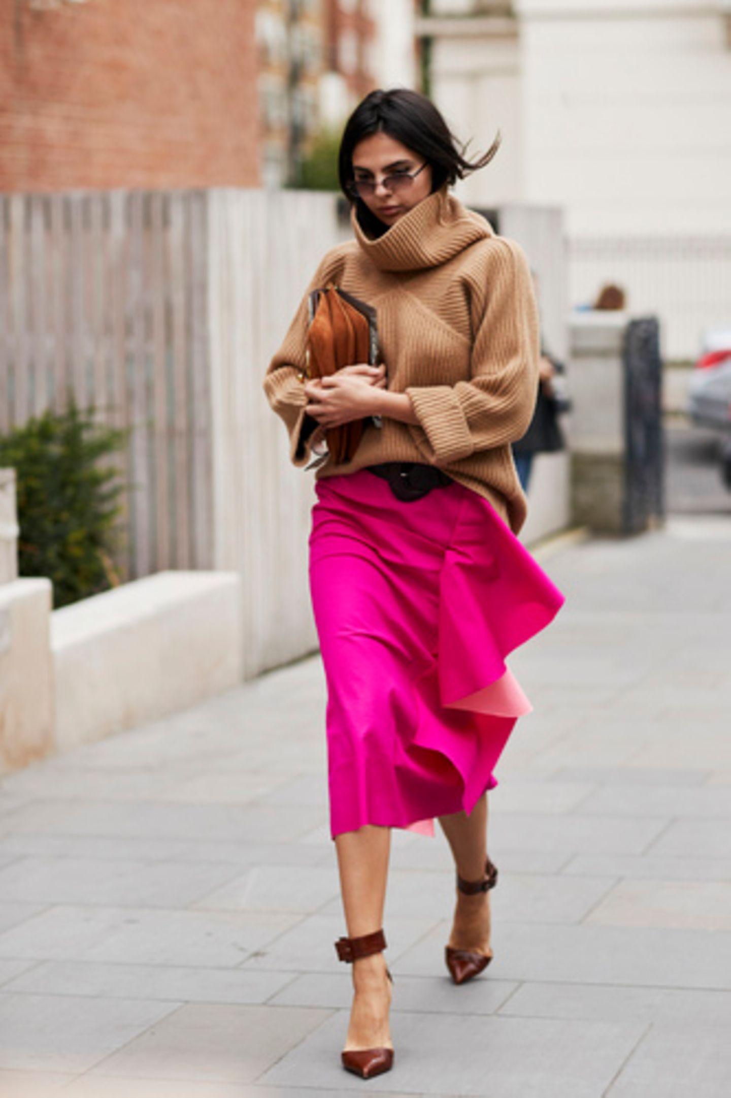 Camelpullover und pinker Seidenrock