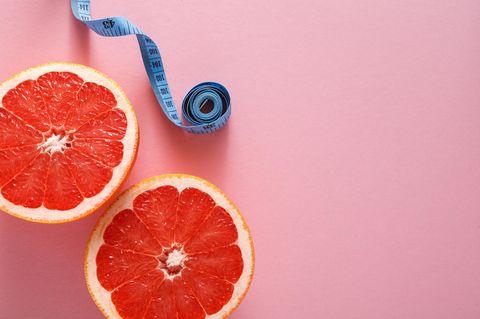 Nulldiät: Grapefruits und Maßband auf pinkem Hintergrund