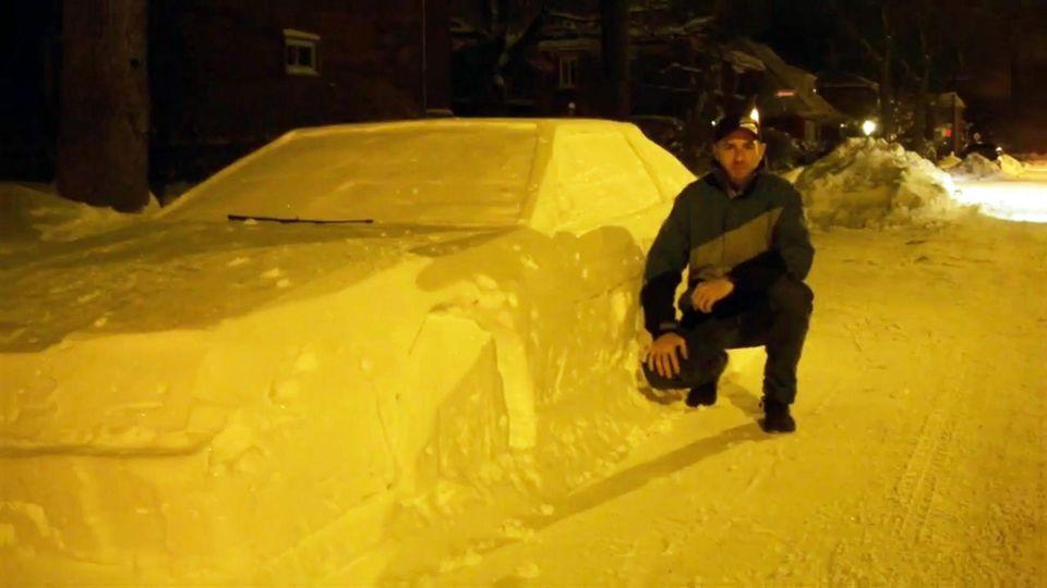 Schnee-Auto: Polizist macht Selfie mit Skulptur