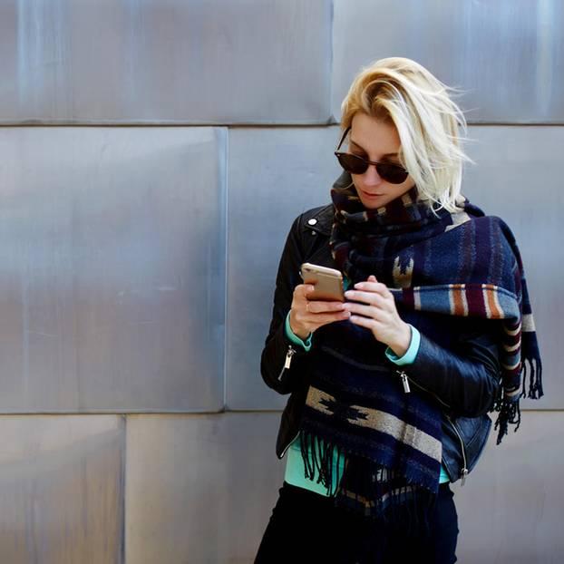 Inklumojis: Eine junge, hippe Frau lehnt an einer Wand und guckt auf ihr Handy