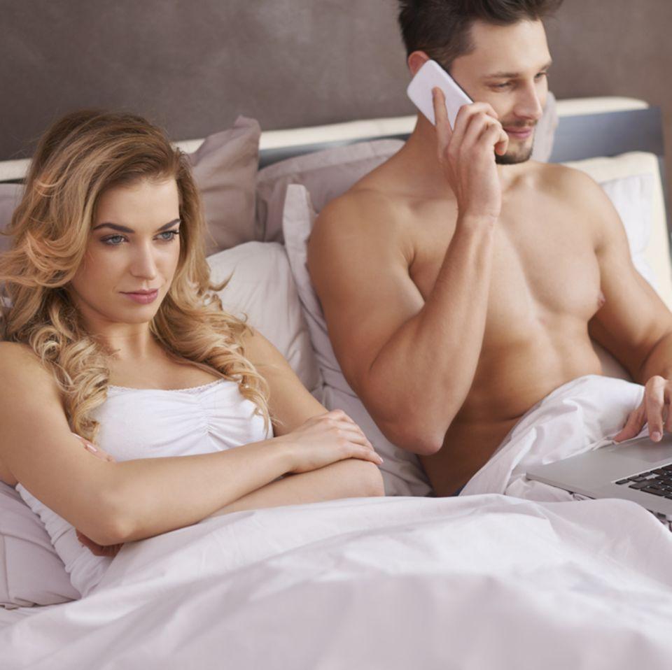 Fernseher im Schlafzimmer: Halbnacktes Paar guckt unbefriedigt im Bett auf den Fernseher