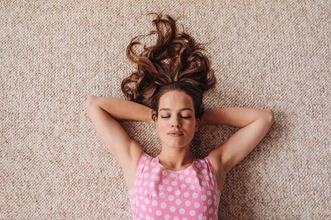 Frau liegt auf Teppich mit geschlossenen Augen und Händen unter dem Kopf