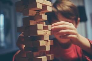 Kind beim Jenga spielen von Michal Parzuchowski – Spiele