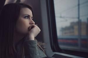 Frau schaut nachdenklich aus Zug – Depression