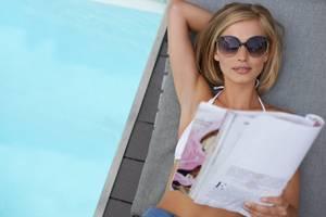 Horoskope lesende Frau am Pool