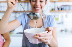 Kohlsuppendiät: Frau mit Suppenkelle füllt Suppenteller auf