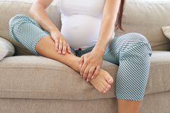 27. SSW: Schwangere sitzt mit dicken Beinen auf dem Sofa