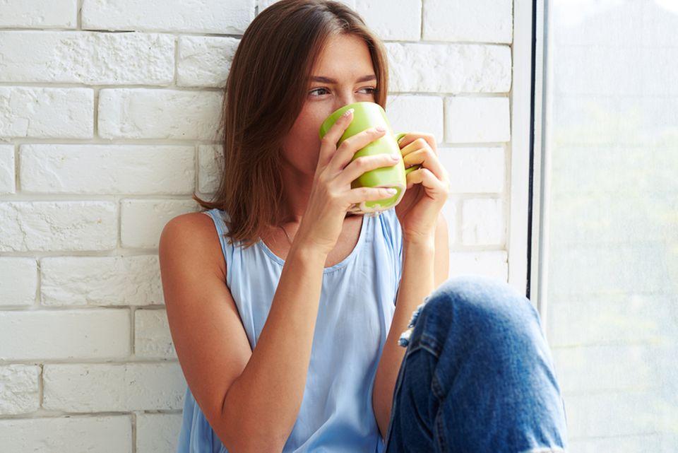 Wirkung von Kaffee auf die Haut: Frau sitzt am Fenster und trinkt aus einer Tasse